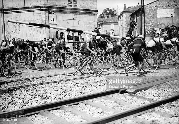 Racers trying to cross the railway tracks with their bicycles on their shoulders during the 1939 Tour de France at Tonnay in the Charente department...