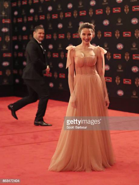 Rachael Finch poses as Brendan Fevola is seen in the background ahead of the 2017 Brownlow Medal at Crown Entertainment Complex on September 25 2017...