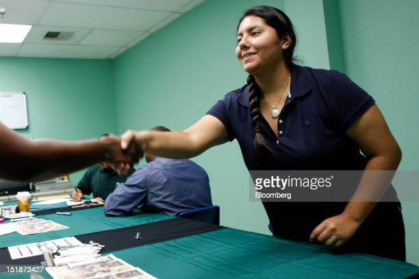 Rachael George shakes the hand of Anna Martinez-Montes after offering her a job during a hiring fair for the renovated West Los Angeles Orchard...