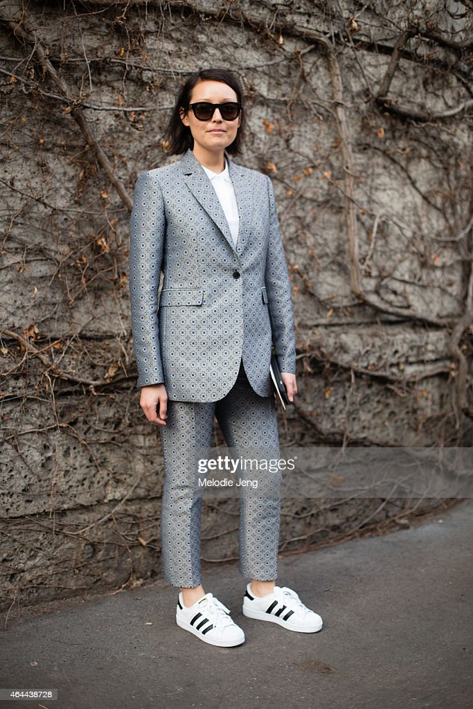 Rachael Wang of Style.com wears a Joseph suit with Saint Laurent sunglasses and Adidas original sneakers on February 25, 2015 in Milan, Italy.