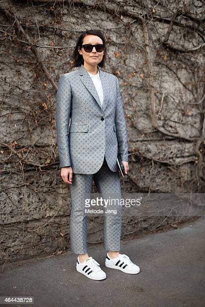 Rachael Wang of Stylecom wears a Joseph suit with Saint Laurent sunglasses and Adidas original sneakers on February 25 2015 in Milan Italy