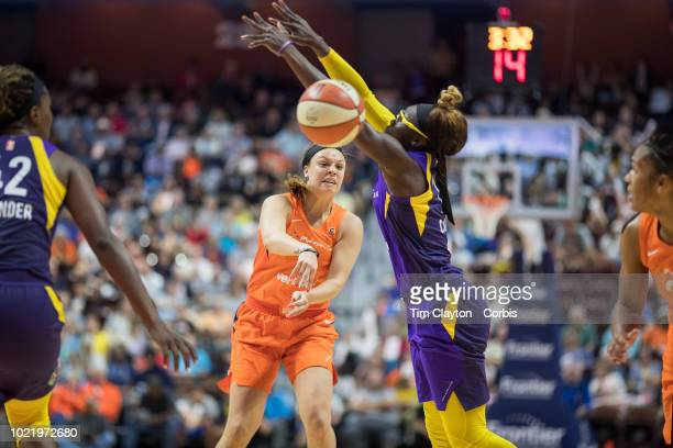 Rachel Banham of the Connecticut Sun feeds a pass to Alyssa Thomas of the Connecticut Sun as Essence Carson of the Los Angeles Sparks defends during...