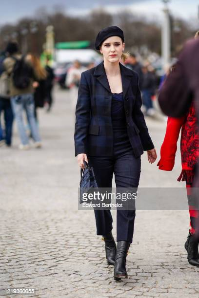 Rachel Brosnahan wears a beret hat, a navy dark blue checkered blazer jacket, a top, cropped pants, black leather boots, a Dior mini shopping bag,...