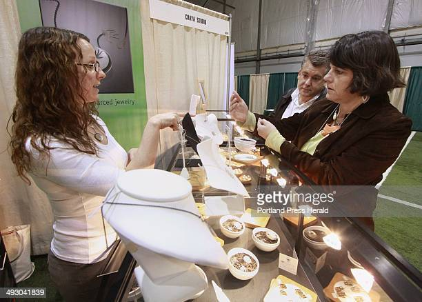 Rachel Chaya Caron of Chaya Studio shows jewelry to Teresa and David Beaudoin at the trade show David Beaudoin is hotel manager at Hollywood Slots in...