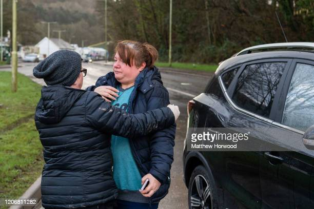 Rachel Cox hugs a family member after her brand new MG car is found having floated 250 metres down the road due to flooding on Oxford Street on...