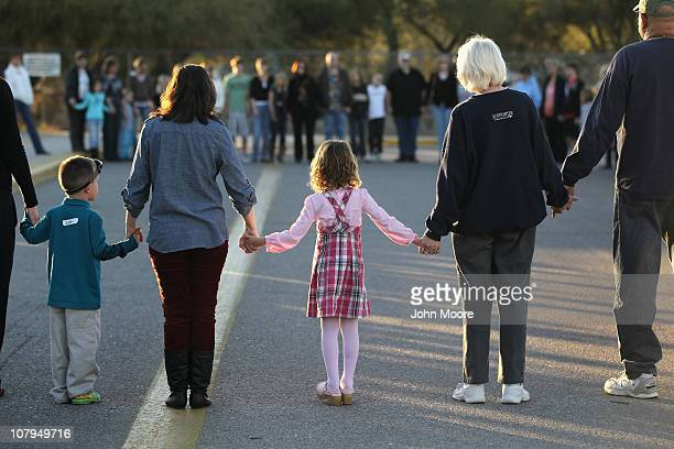 Rachel Crabb 5yearsold holds hands with teachers parents and other students during a moment of silence for her slain schoolmate Christina Green at...