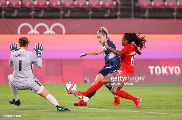 Rachel Daly of Team Great Britain shoots whilst under pressure from Stephanie Labbe and Ashley Lawrence of Team Canada during the Women's Group E...