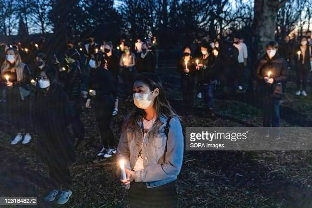 Rachel Dumke of Columbus Ohio holds a lit candle as she stands in solidarity with others at a vigil for the eight victims of the shooting in Atlanta,...