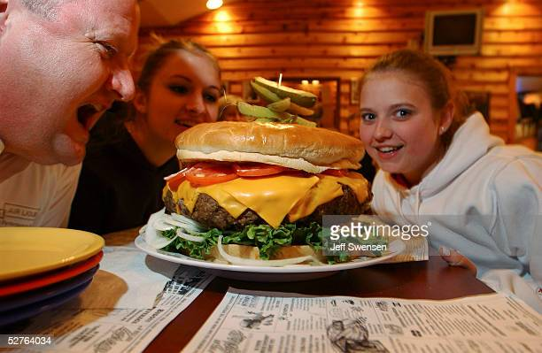 Rachel Fleagle her sister Jessica and Scott Staub all of Philadelphia pose with the burger May 5 2005 at Denny's Beer Barrell in Clearfield...