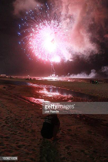 Rachel Hinson takes a photograph as the 4th of July fireworks light up a slick of oil on the beach after it washed ashore from the Deepwater Horizon...