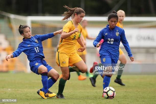 Rachel Lowe of Australia is challenged by Anuthida Malasri and Tarntip Pandech of Thailand during the International match between the Young Matildas...