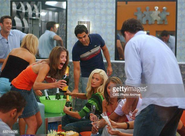 Rachel Plencner from Parker Colorado pours champagne for fellow houseguests Janelle Pierzina from Miami Beach Florida Jennifer Vasquez from Plano...