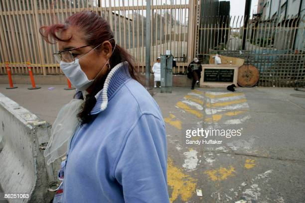 Rachel Rodriguez walks towards the United States-Mexico border while wearing a surgical mask at the Port of Entry on April 27, 2009 in Tijuana,...
