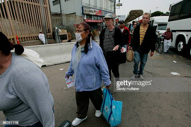 Rachel Rodriguez , walks towards the United States-Mexico border while wearing a surgical mask at the Port of Entry on April 27, 2009 in Tijuana,...