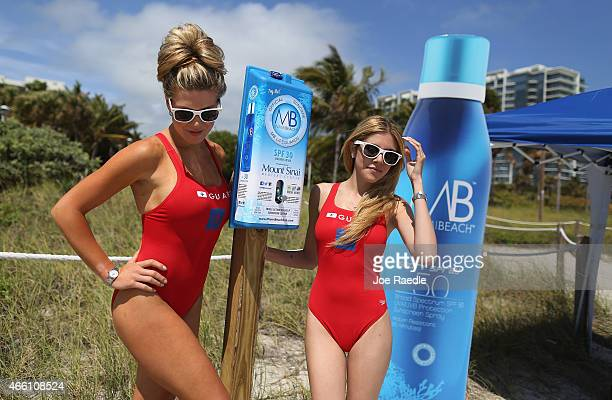 Rachel Scherdin and Caroline Oliveira help unveil one of 50 sunscreen dispensers that are being setup along the beach on March 13 2015 in Miami Beach...