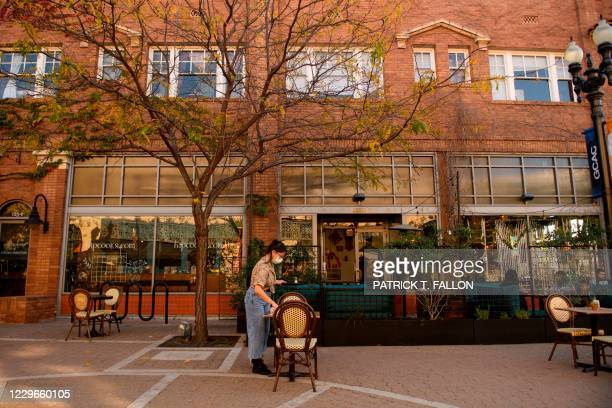 Rachel Thorlund, manager at The Den Cafe, clears an outdoor table following reimposed restrictions on indoor dining in Orange County due to Covid-19...
