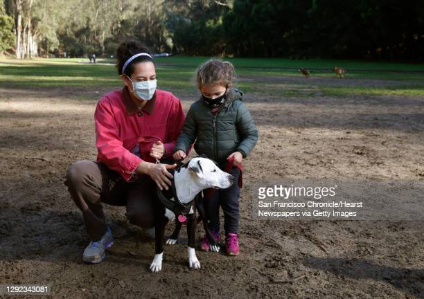 Rachel Whiteside-Rosen and daughter Ella visit the Stern Grove off-leash dog park with 6-month-old puppy Bean in San Francisco, Calif. On Thursday,...