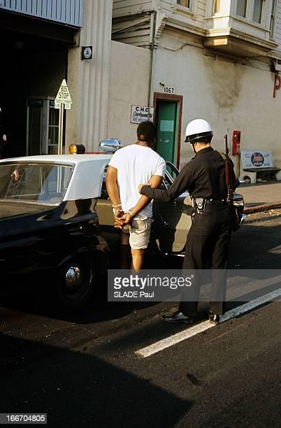 Racial Riots In Los Angeles In 1965 En août 1965 à Los Angeles dans une rue du quartier noir de Watts un policier en uniforme faisant entrer dans une...