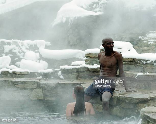 racially mixed couple in hot springs pool, man sitting on steps - steamboat springs colorado - fotografias e filmes do acervo