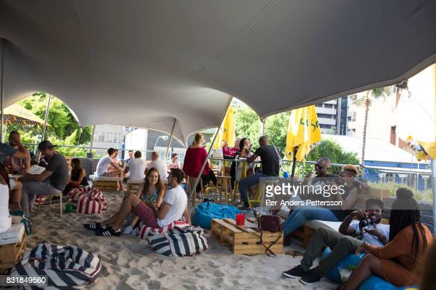 A racially mixed crowd enjoys a beach themed bar on March 19 2016 in Braamfontein in downtown Johannesburg South Africa The area a culture hub with...