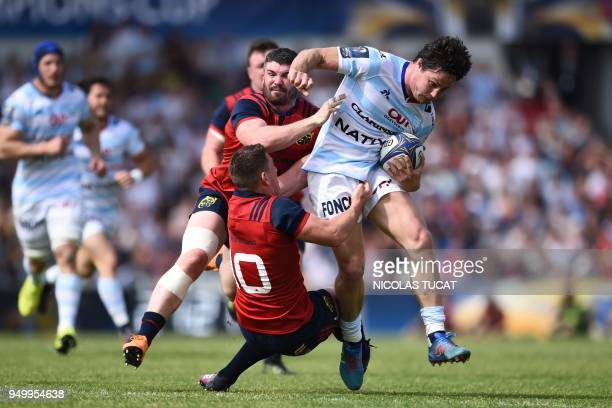 Racing 92's French centre Henry Chavancy is tackled by Munster's Irish centre Sammy Arnold and Munster's Irish flyhalf Ian Keatley during the...