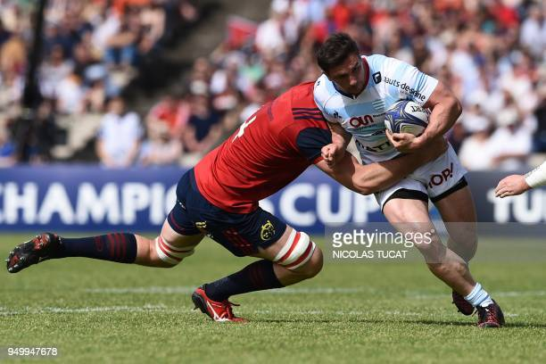 Racing 92's French centre Henry Chavancy is tackled by Munster's South African lock Jean Kleyn during the European Champions Cup semifinal rugby...