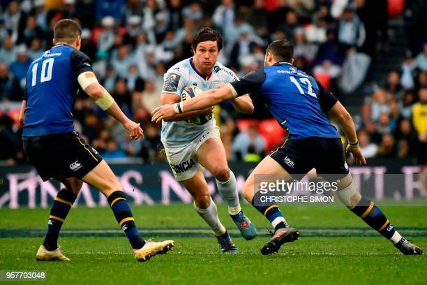 Racing 92's French centre Henry Chavancy tries to escape a tackle by Leinster's Irish flyhalf Johnny Sexton and Leinster's Irish centre Robbie...