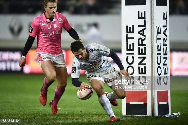 Racing 92's French fullback Brice Dulin scores a try despite of Stade Francais' French flyhalf Jules Plisson during the French Top 14 rugby union...