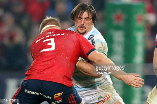 Racing 92's French hooker Camille Chat is tackled by Munster's Irish prop John Ryan during the European Champions Cup Pool 4 rugby union match...