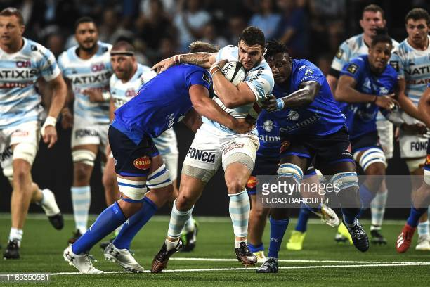 TOPSHOT Racing 92's French hooker Teddy Baubigny is tackled by Castres' players during the French Top 14 rugby union match between Racing 92 and...
