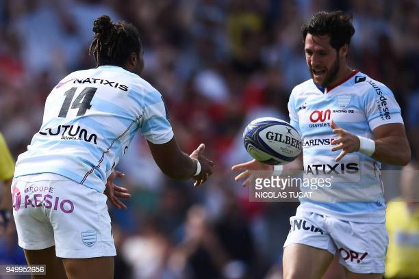 Racing 92's French winger Teddy Thomas passes the ball to Racing 92's French scrumhalf Maxime Machenaud to score a try during the European Champions...