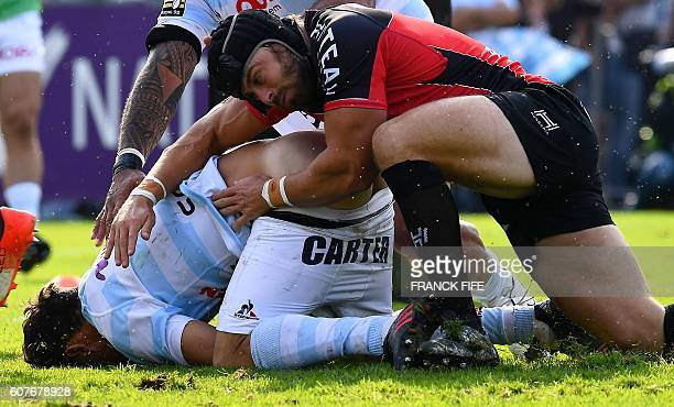 Racing 92's New Zealander flyhalf Dan Carter is tackled by Toulon's Welsh fullback Leigh Halfpenny during French Top 14 rugby union match between...