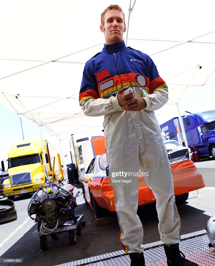 Racing car driver in garage, portrait : Stock Photo