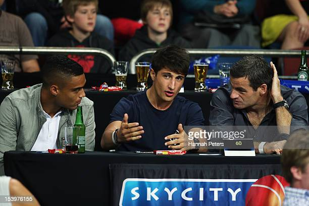Racing car driver Mitch Evans talks with All Whites Winston Reid and Ryan Nelsen during the round two NBL match between the New Zealand Breakers and...