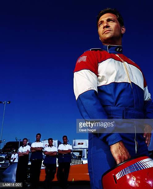 racing car driver, pit crew in background - レーシングドライバー ストックフォトと画像