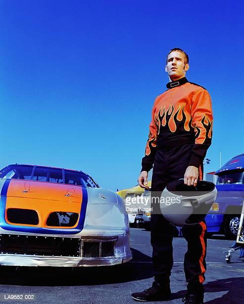 racing car driver standing by racing car - レーシングドライバー ストックフォトと画像
