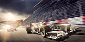 Racing Car During Race on Track At Sunset