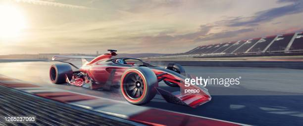 racing car moving at speed on race track at sunset - grand prix motor racing stock pictures, royalty-free photos & images