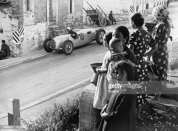 A racing car on a street with spectators Pescara Italy Photograph August 15th 1937
