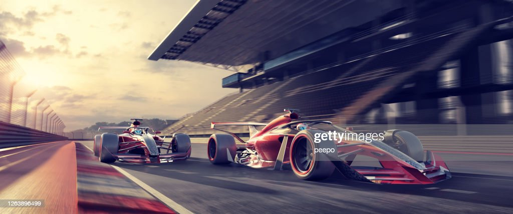 Racing Cars Moving Fast On Racetrack Near Grandstand At Sunset : Stock Photo