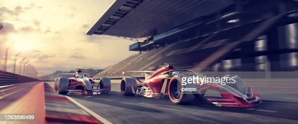 racing cars moving fast on racetrack near grandstand at sunset - sports race stock pictures, royalty-free photos & images