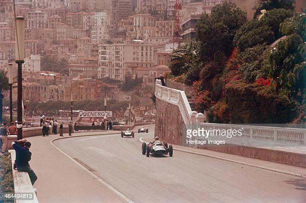 Racing cars on the road track at the Monaco Grand Prix, Monte Carlo. The town of Monte Carlo can be seen rising up the hill in the distance.
