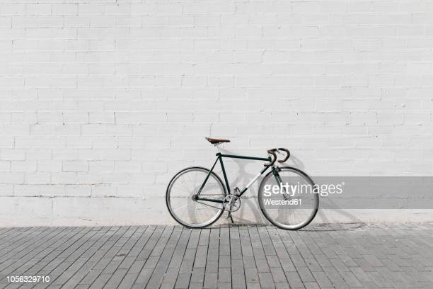 racing cycle leaning against wall - racing bicycle stock pictures, royalty-free photos & images