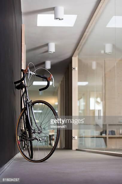 Racing cycle standing in corridor of modern office