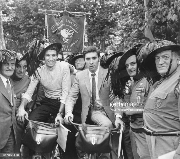 Racing cyclists Felice Gimondi of Italy and Eddy Merckx of Belgium with members of the Italian Bersaglieri corps during celebrations of the centenary...