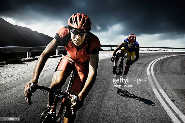 racing cyclists on road - rivaliteit stockfoto's en -beelden