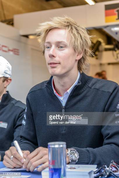 Racing driver Brendon Hartley signing cards during the pitwalk before the race in front of the Porsche pit box with the Porsche 919 Hybrid...