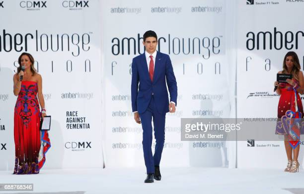 Racing driver Esteban Ocon walks the runway as presenters Natalie Pinkham and Federica Masolin look on at the Amber Lounge Fashion Monaco 2017 at Le...