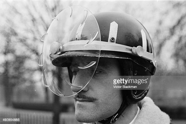 Racing driver Graham Hill demonstrating the new rain proof safety helmet, April 16th 1964.
