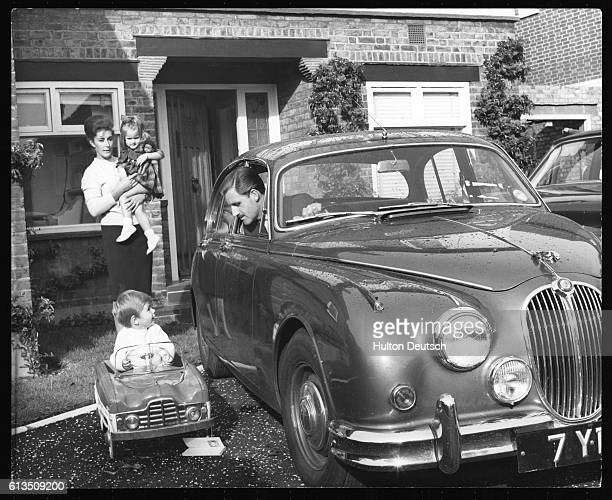 Racing driver Graham Hill with his family. His son Damon plays with a toy car as his parents and sister Brigitte look on.
